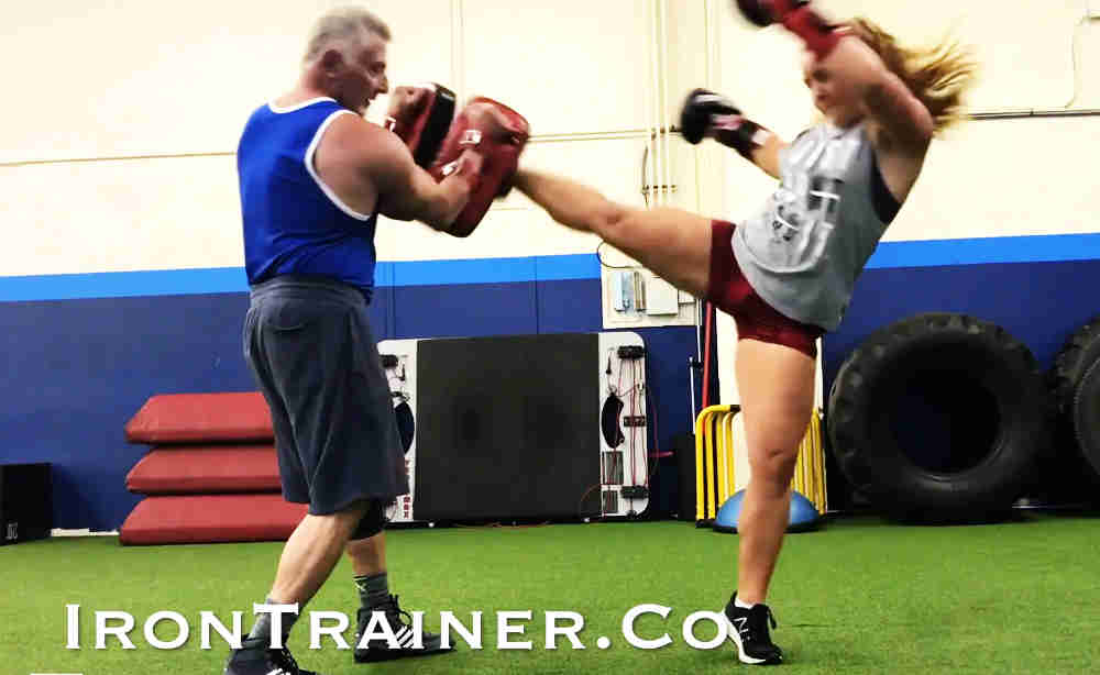 kickboxing trainer holding thai pads while client kicks pads adding foot pivot